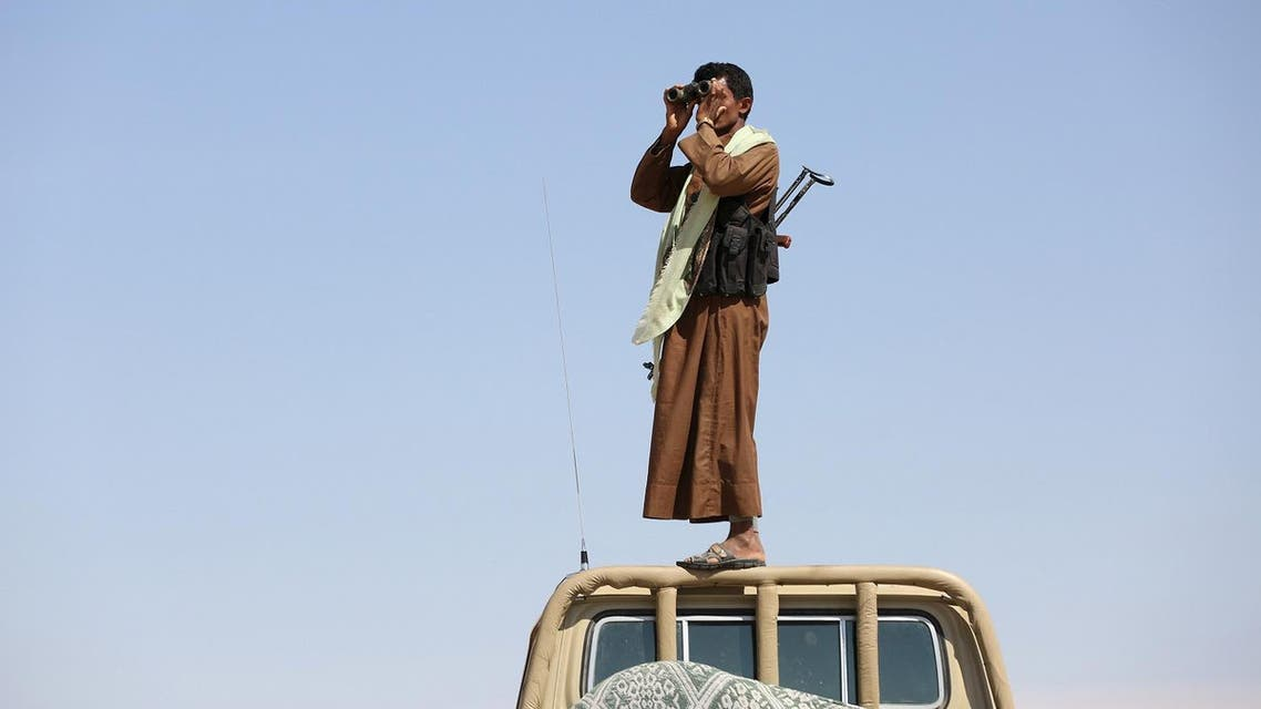 A tribal fighter loyal to Yemen's government stands on the roof of a pick-up truck as he uses binoculars to look at Houthi positions between al-Jawf and Marib on December 5, 2015. (Reuters)