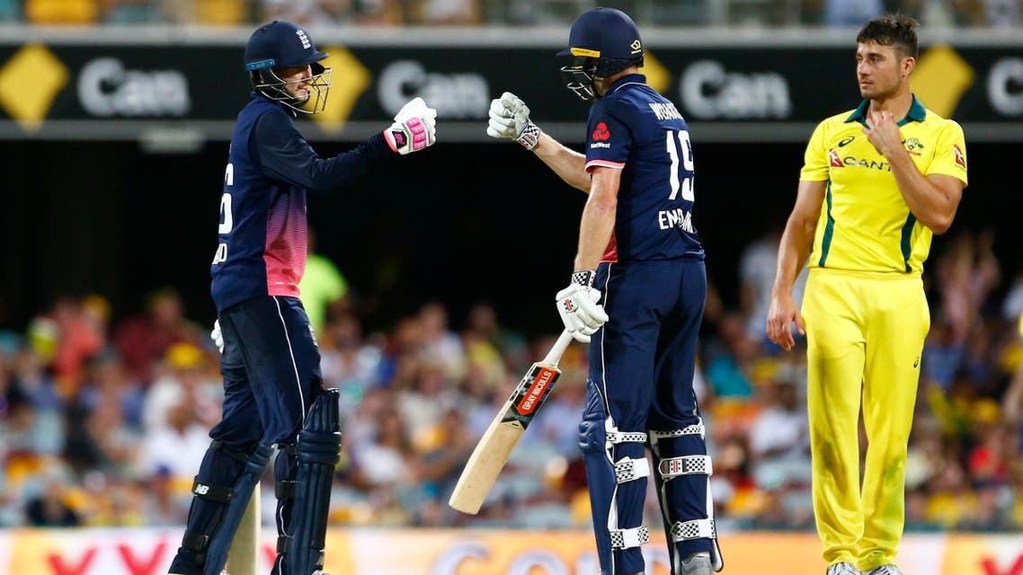 England's Joe Root (left) and Chris Woakes (center) celebrate victory as Australia's Marcus Stoinis looks on, during the ODI cricket match between England and Australia in Brisbane on January 19, 2018. (AFP)