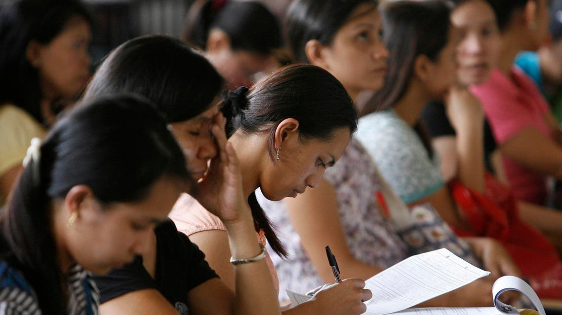 A woman fills an application form for a job posting in Kuwait during a job fair in Manila on September 20, 2010. (Reuters)