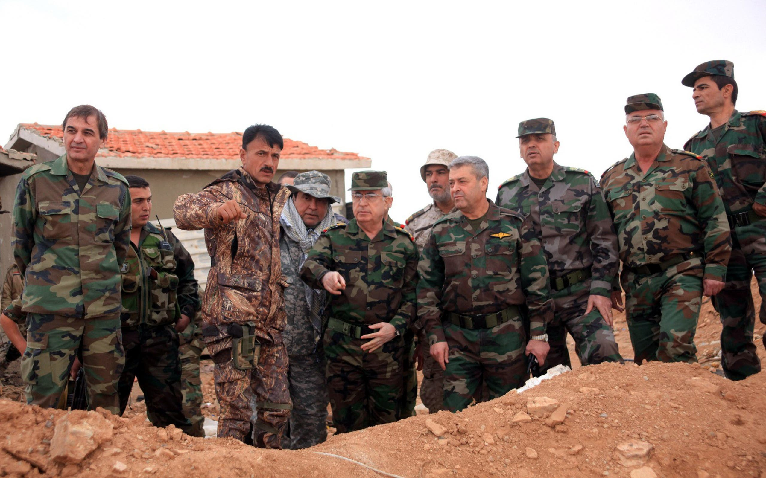 A handout picture released by the Syiran Arab News Agency (SANA) shows Chief of the General Staff of the Syrian Army Ali Abdullah Ayyoub (C), accompanied by a number of senior army officers during fighting in 2014. (AFP, SANA)