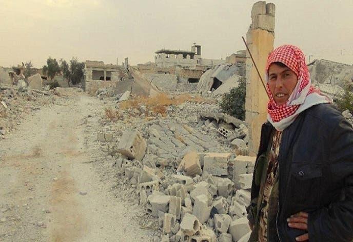 أم عبود أمام أنقاض البيوت في بلادها التي دمرها النظام وشرد شعبها