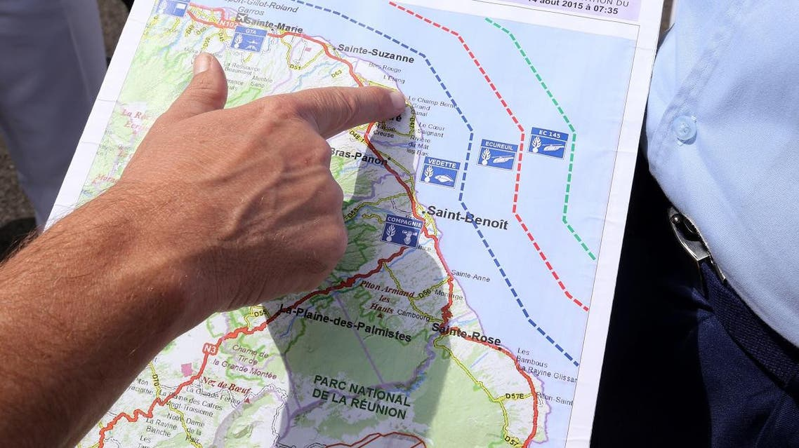 French maritime gendarmes look at a map indicating measures being undertaken in the search for wreckage from the missing MH370 plane at the marina of Saint-Marie on the French island of La Reunion on August 14, 2015. (AFP)