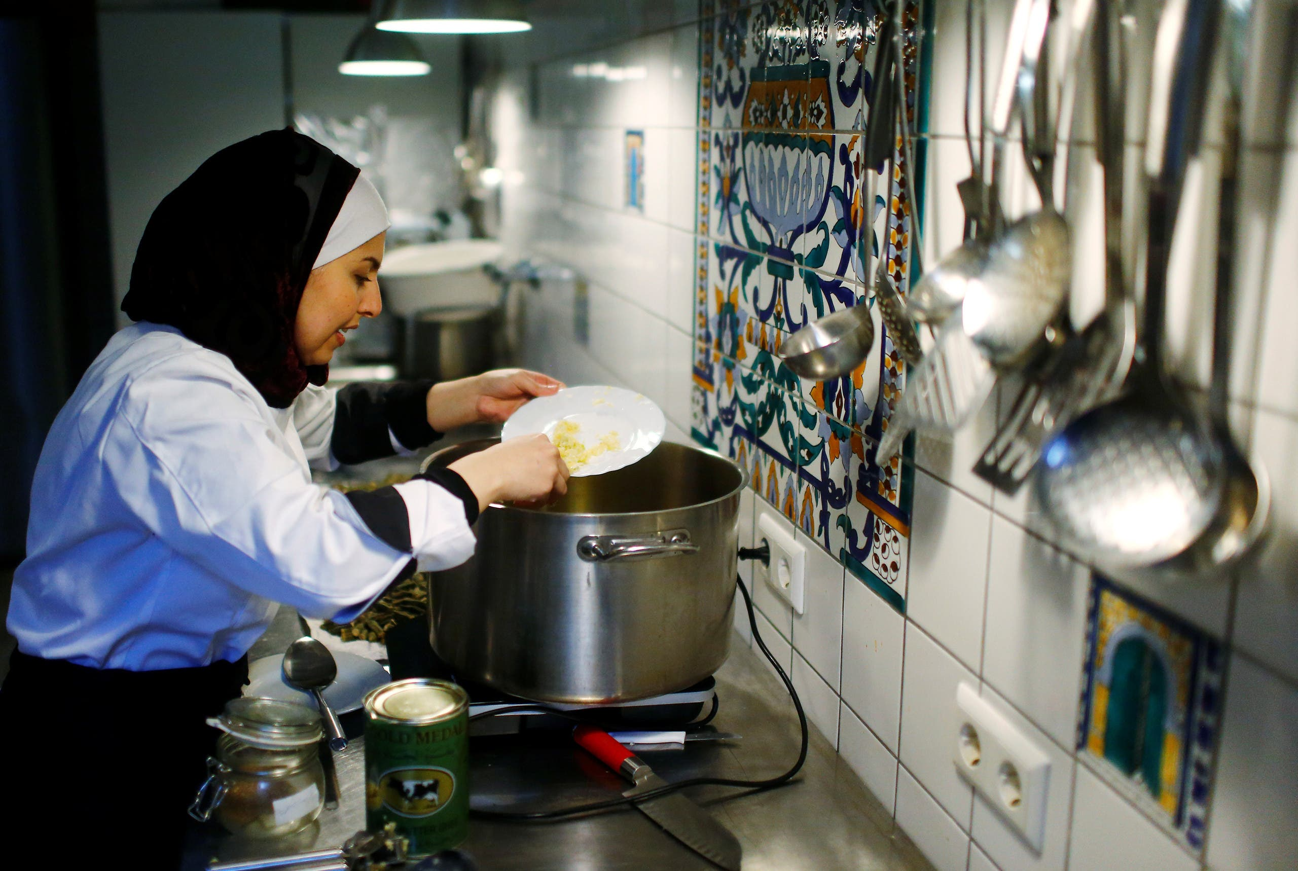 Syrian migrant Malakeh Jazmati cooks in a kitchen of Cafe in Berlin, Germany January 23, 2018. REUTERS