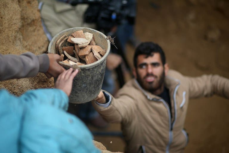 Abdul Karim al-Kafarnah, a Palestinian resident of Beit Hanun, passes on a bucket full of pottery fragments at a freshly-discovered cemetery in the garden of his house in the town in the northern Gaza Strip, on January 26, 2018. Experts said the graves were part of a loculus tomb that possibly dates from the late Roman-Byzantine era in the fourth to sixth century CE. MOHAMMED ABED / AFP