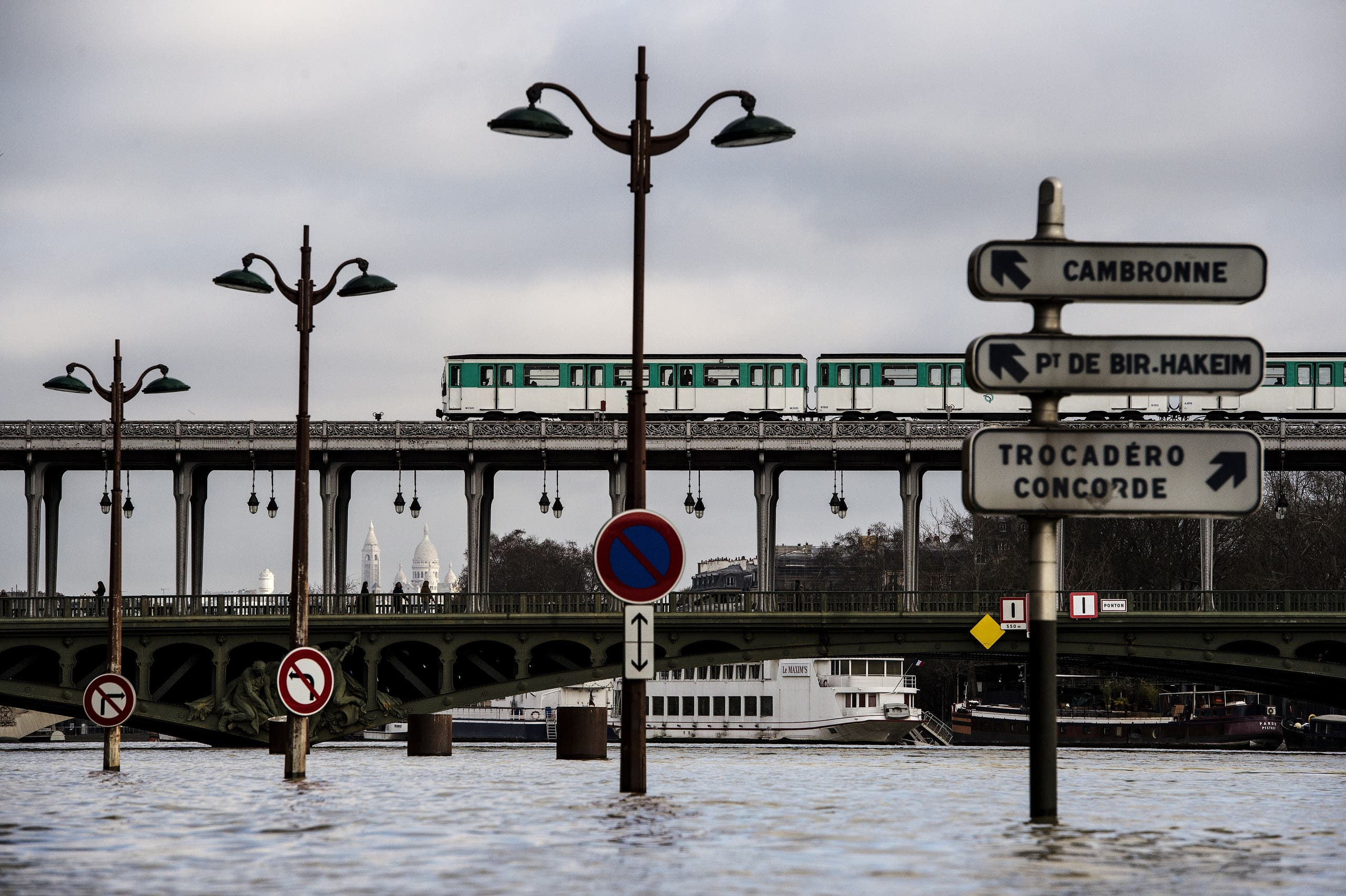 Pedestrians and a metro train cross the swollen Seine river on the Bir-Hakeim bridge in Paris on January 26, 2018. (AFP)
