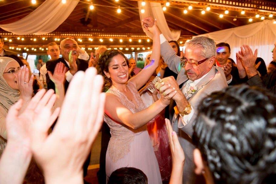 صورة لحفل يبدو أنه عائلي، وفيه شبكت يديها بيدي والدها، ورقصا معاً