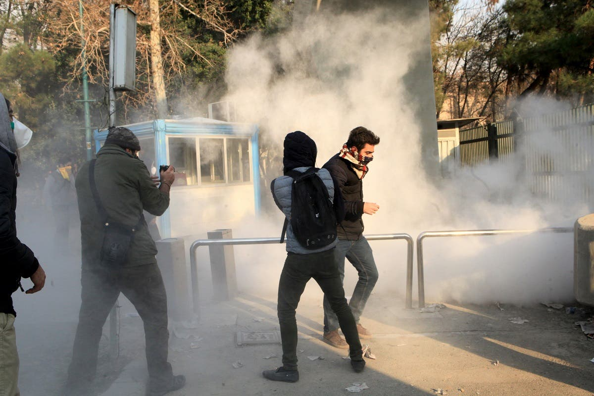 Iranian students run for cover from tear gas at the University of Tehran during a demonstration driven by anger over economic problems, in the capital Tehran on December 30, 2017. Students protested in a third day of demonstrations, videos on social media showed, but were outnumbered by counter-demonstrators.  STR / AFP