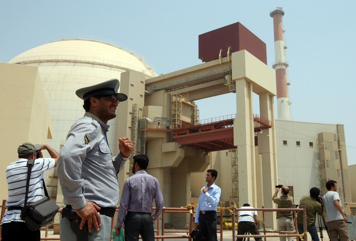 An Iranian security man stands next to journalists outside the reactor building at the Russian-built Bushehr nuclear power plant in southern Iran on August 21, 2010 during a ceremony initiating the transfer of Russia-supplied fuel to the facility after more than three decades of delay. AFP PHOTO/ATTA KENARE ATTA KENARE / AFP