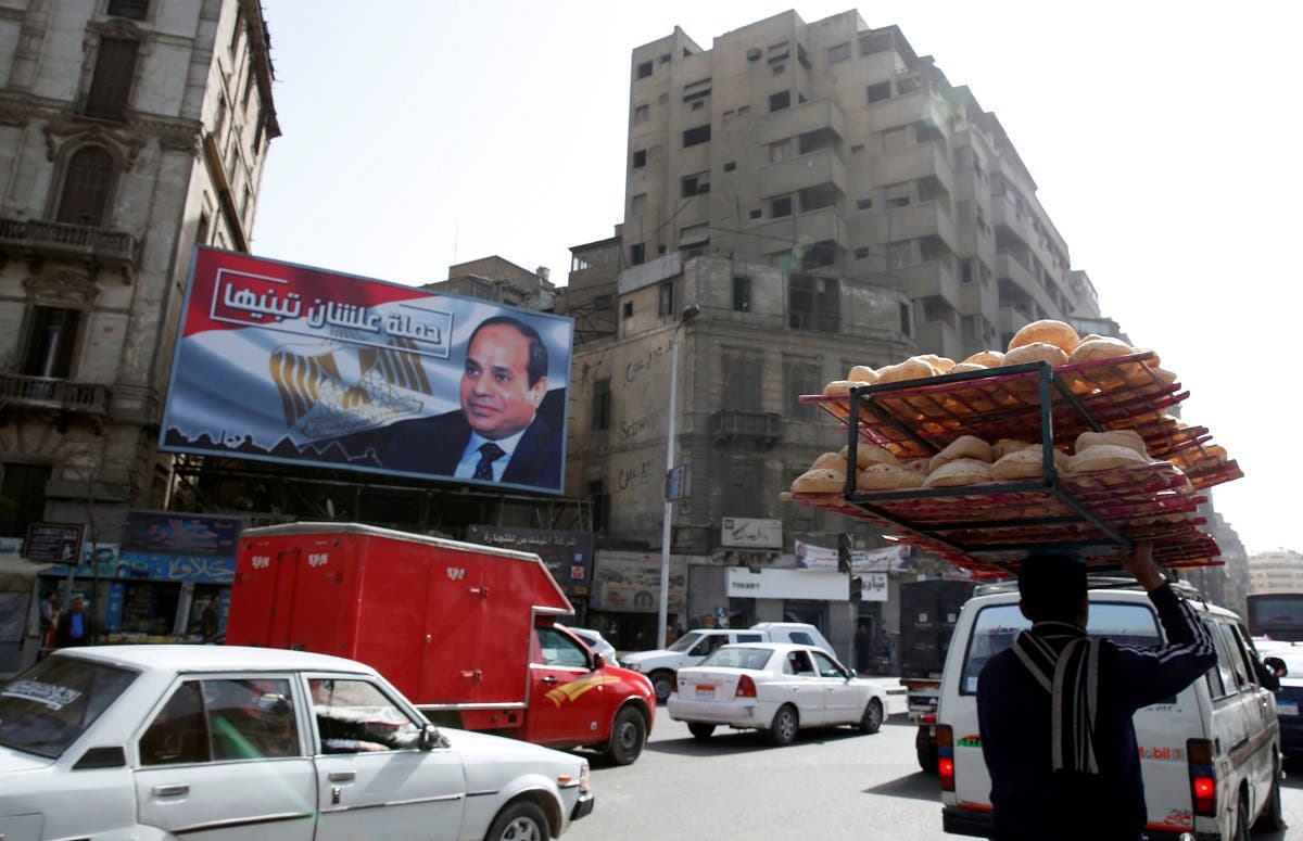 A man rides a bicycle as he carries breads on his head along a busy street near a poster of Egypt's President Abdel Fattah al-Sisi from his campaign. (Reuters)
