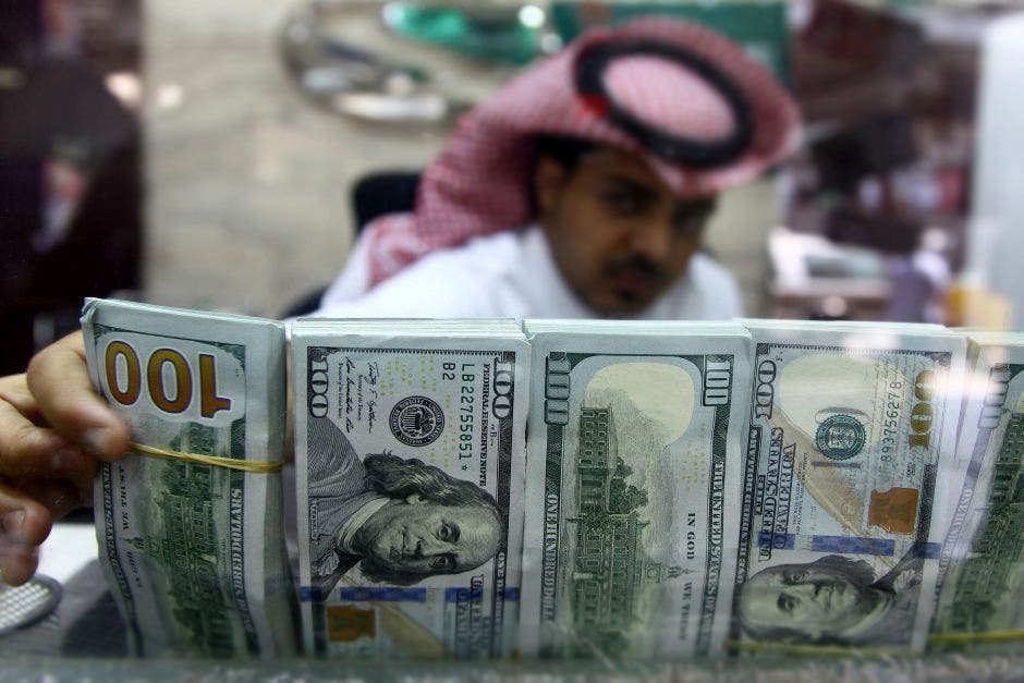A Saudi money changer, pictured through a glass, arranges U.S banknotes at a currency exchange shop in Riyadh. (Reuters)