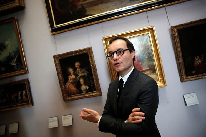 Head of the paintings department at the Louvre museum, Sebastien Allard, answers reporters next to paintings looted by Nazis during World War II, in Paris, Tuesday, Jan. 30, 2018. (AP)