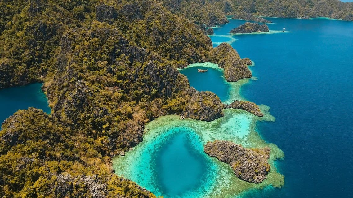 Aerial view: Mountain Barracuda lake, on tropical island, Lagoon with blue, azure water. Lake in the mountains covered with tropical forest on the island Coron, Palawan, Philippines. (Shutterstock)