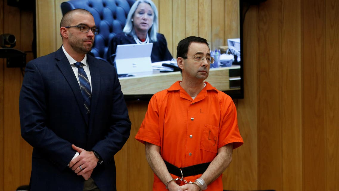 Larry Nassar, a former team USA Gymnastics doctor who pleaded guilty in November 2017 to sexual assault charges, stands with his attorney Matt Newburg as Judge Janice Cunningham (seen on screen) gives instructions during Nassar's second sentencing in the Eaton County Circuit Court in Charlotte, Michigan, U.S., January 31, 2018. REUTERS/Rebecca Cook