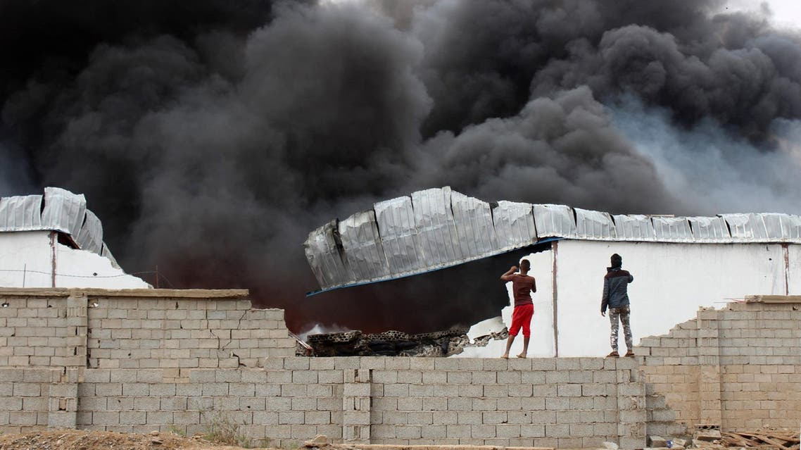 Yemeni take photos of smoke rising from inside a military camp in the northern Dar Saad district of Aden on January 31, 2018. (AFP)