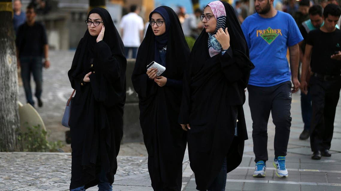"""Iranian women make their way in a sidewalk while wearing the """"chador,"""" in downtown Tehran on Aug. 24, 2017. (AP)"""
