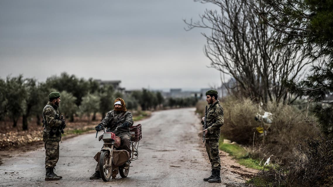 A Turkish-backed Syrian rebel fighter stops a armed man near the frontline on January 26, 2018 at the Syrian town of Azaz. (AFP)