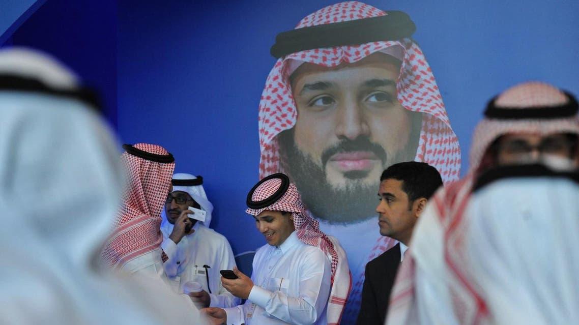 Saudi men chat in front of a poster of Saudi Crown Prince Mohammed bin Salman in Riyadh. (Photo: AFP)