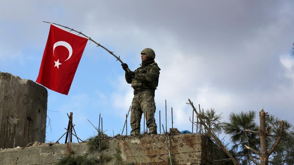 A Turkish soldier waves a flag on Mount Barsaya, northeast of Afrin. (Reuters)