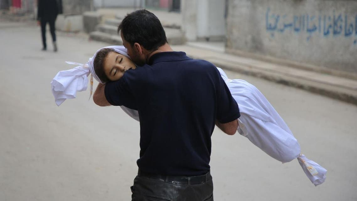 A Syrian father kisses the body of his daughter, 6-year-old Aya, ahead of her funeral in Zamalka, near Syria's capital Damascus. (AFP)