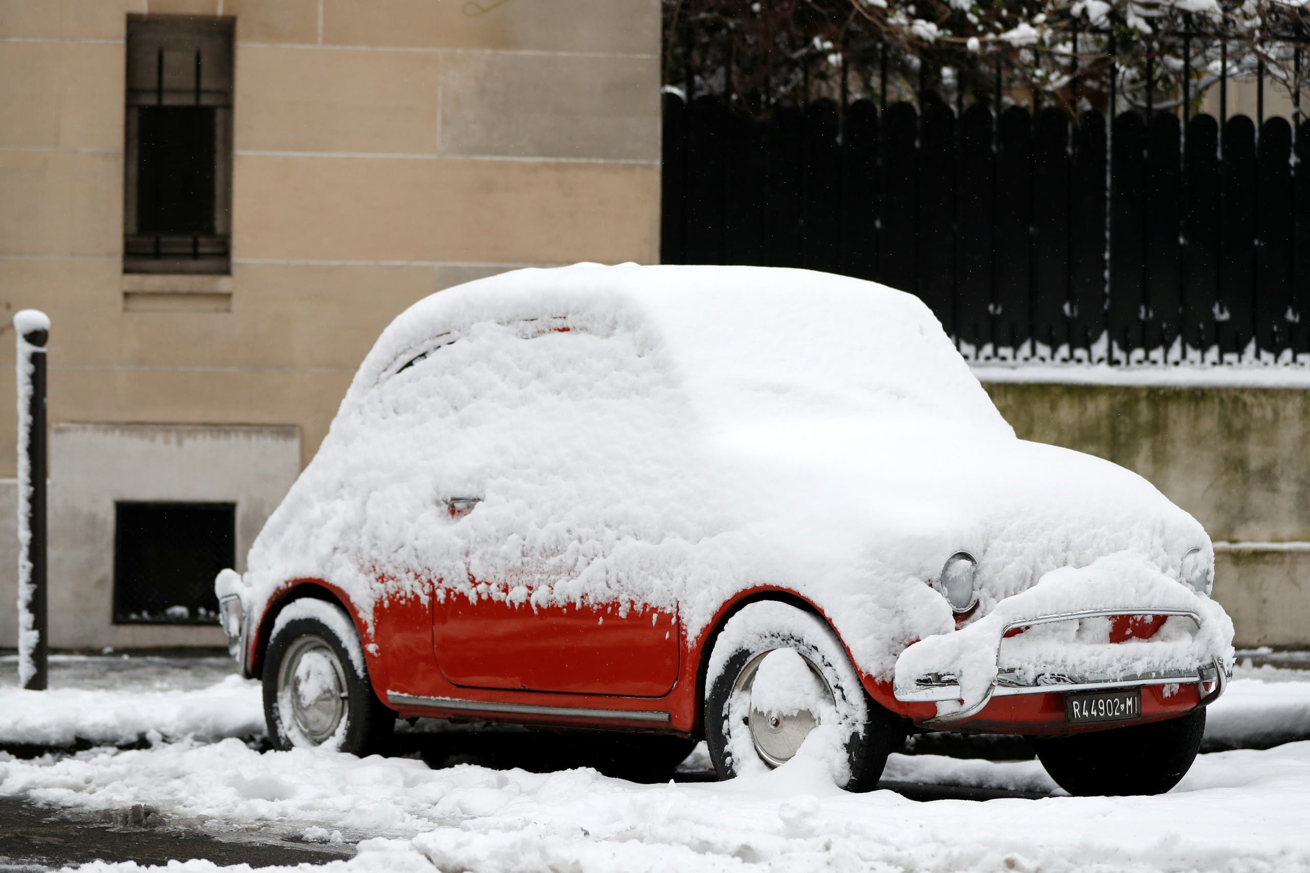 A snow-covered classic car fiat 500 is parked in a street in Paris as winter weather with snow and freezing temperatures arrive in France, February 7, 2018. REUTERS/