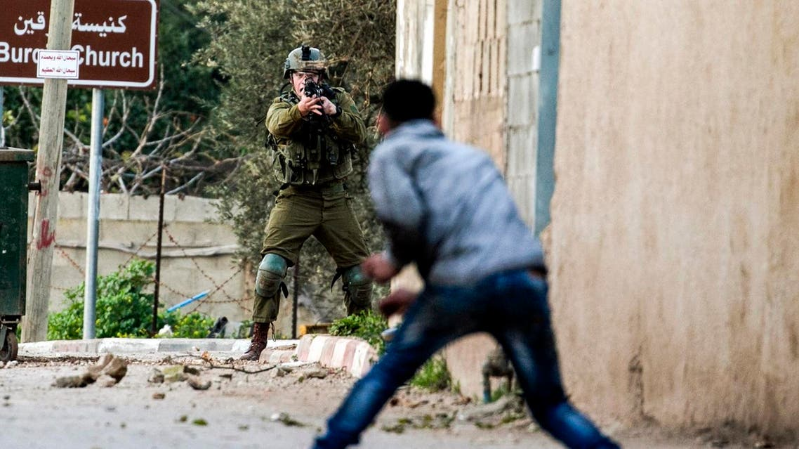 A Palestinian protester confronts an Israeli soldier during an army search operation in the Palestinian village of Burqin in the northern occupied West Bank, on February 3, 2018. (AFP)