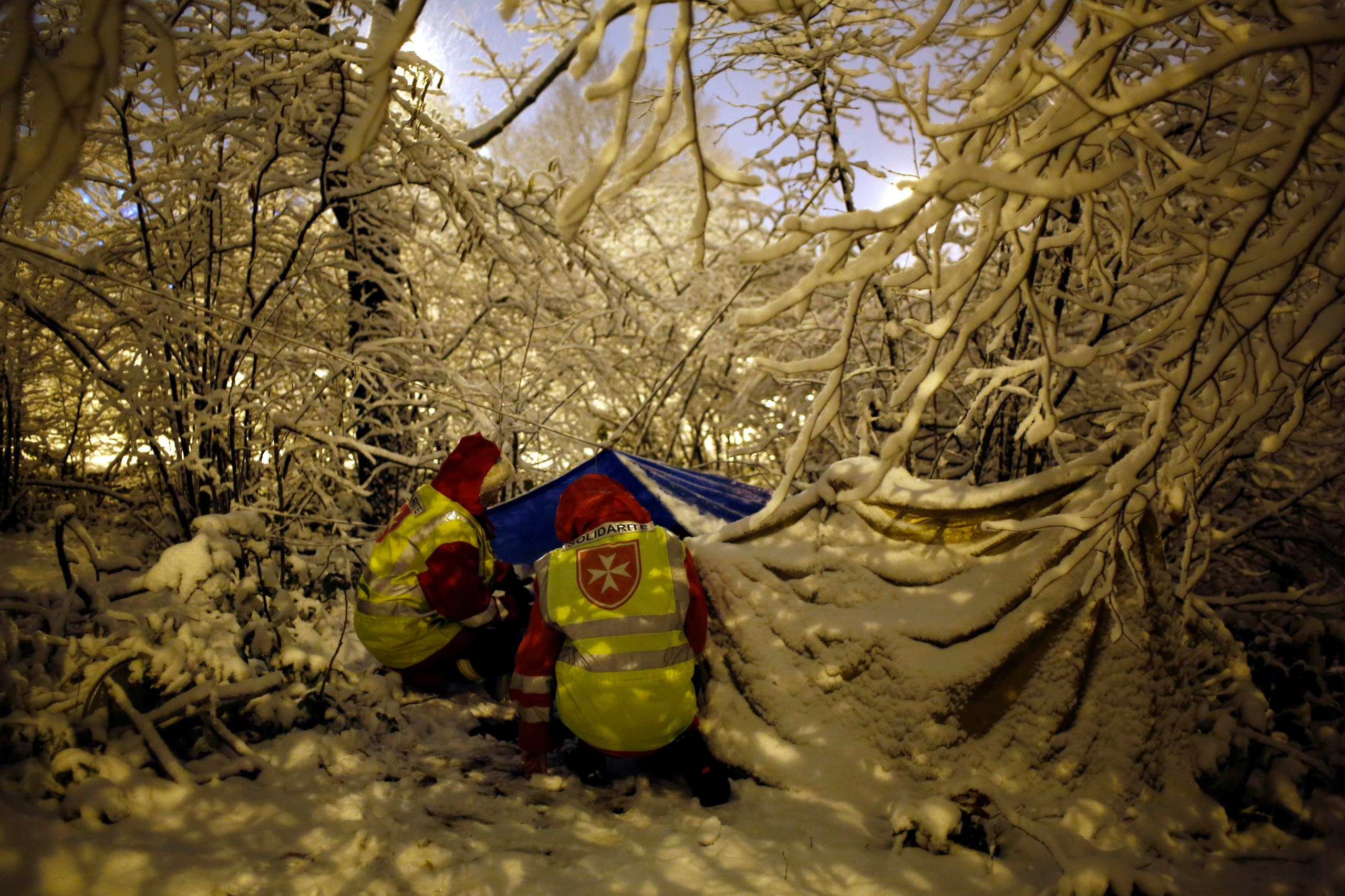 Volunteers from Malta talk with an homeless man in his tent in Boulogne Billancourt, west of Paris, Tuesday, Feb. 6, 2018. France's national weather agency Meteo France said Monday about half the country is on alert for dangerous levels of snow and ice. (AP)
