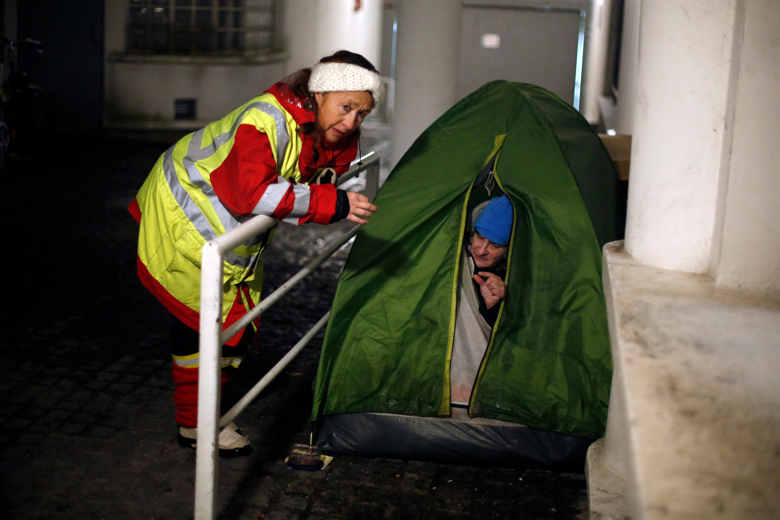 A volunteer worker from Malta, Marie Laure, left, talks with an homeless woman, Marie Luce, during a check on the homeless in Issy les Moulineaux, west of Paris, Tuesday, Feb. 6, 2018. France's national weather agency Meteo France said Monday about half the country is on alert for dangerous levels of snow and ice. (AP Photo)