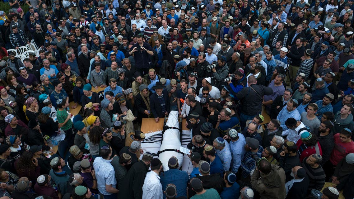 Friends and family mourn by the body of Rabbi Itamar Ben Gal during his funeral in the West Bank settlement of Har Bracha on Feb, 6, 2018. (AP)
