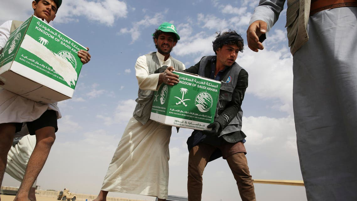 relief workers unload aid carried into Yemen by the Saudi military in Marib, Yemen. (AP)