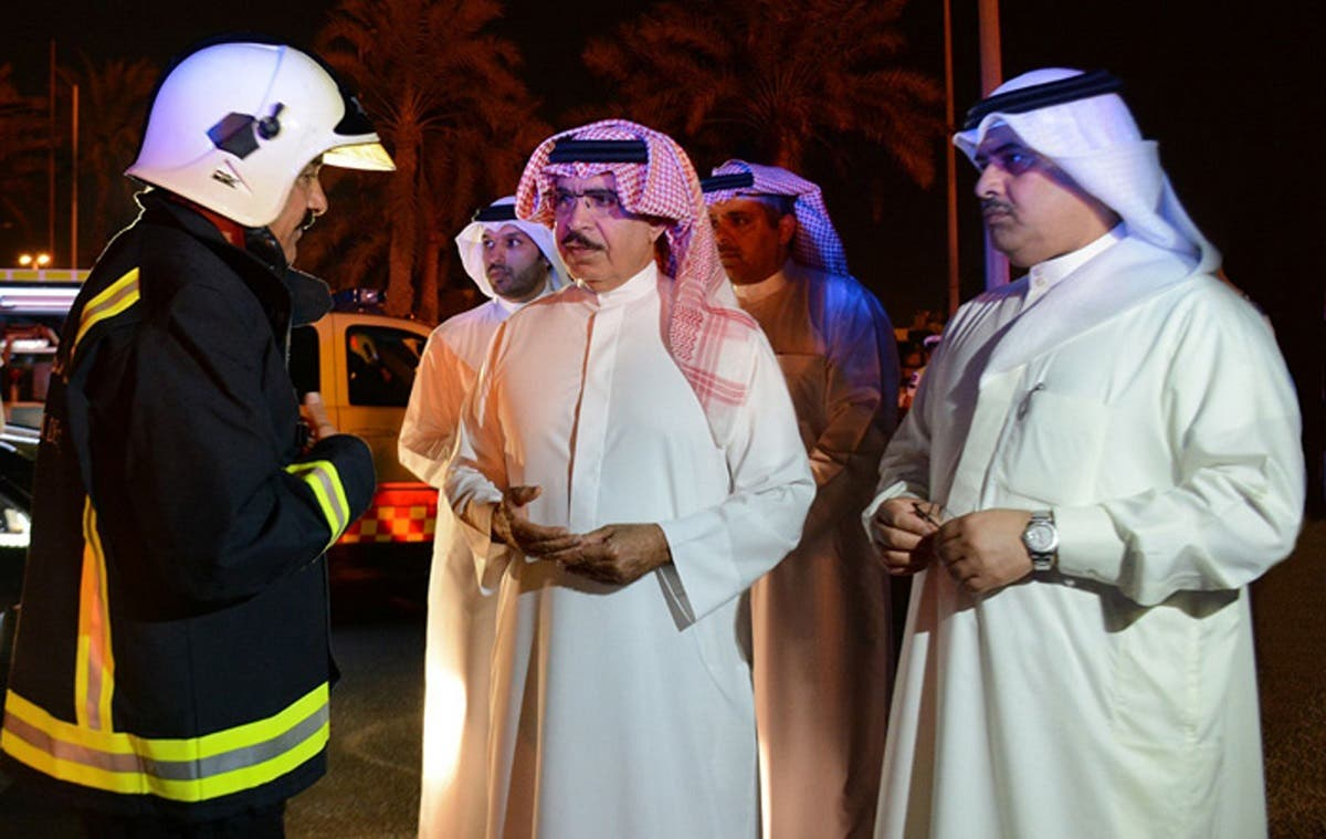 In this photo released by Bahrain News Agency, Sheikh Rashid bin Abdullah Al Khalifa, Bahrain Minister of Interior talks with a member of the emergency services, during his visit to the scene of an explosion, in Bahrain, Saturday, Nov. 11, 2017. Bahrain says an oil pipeline that exploded overnight was attacked by militants in the island nation. (BNA)