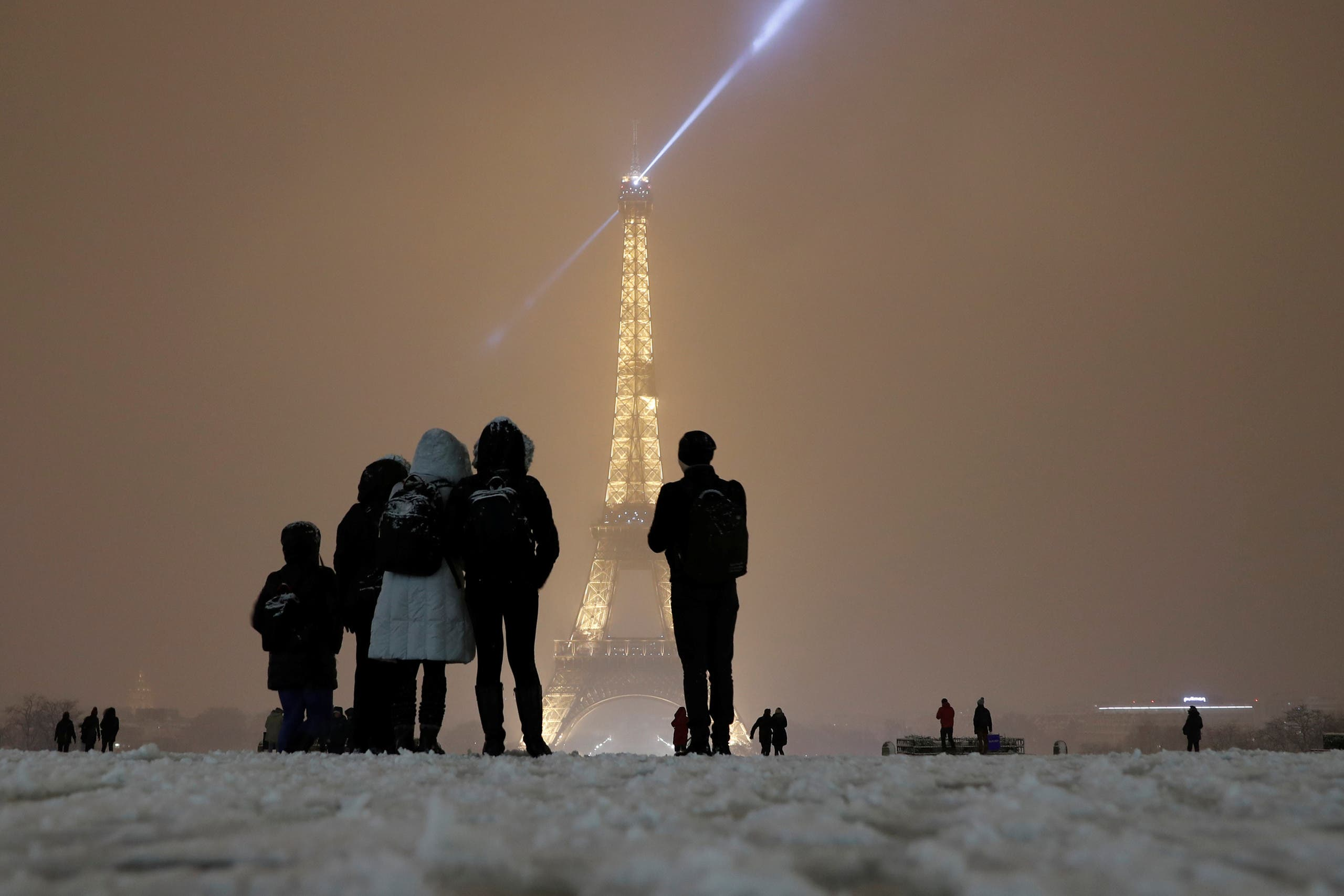 Tourists take pictures as they walk on a snow-covered path near the Eiffel Tower in Paris, as winter weather with snow and freezing temperatures arrive in France, February 6, 2018. Picture taken February 6, 2018. REUTERS