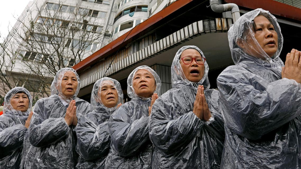 Volunteers pray outside a collapsed building after an earthquake hit Hualien, Taiwan, on February 8, 2018. (Reuters)