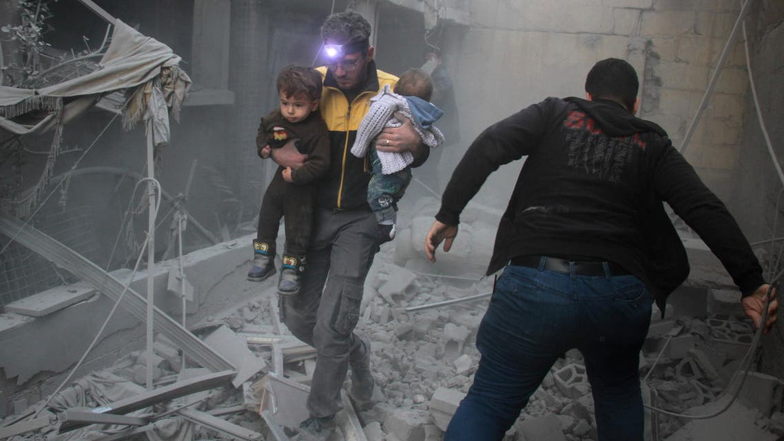 A Syrian man carries two children in the rubble of buildings following regime air strikes on the rebel-held besieged town of Douma in the eastern Ghouta region on February 7, 2018. (AFP)