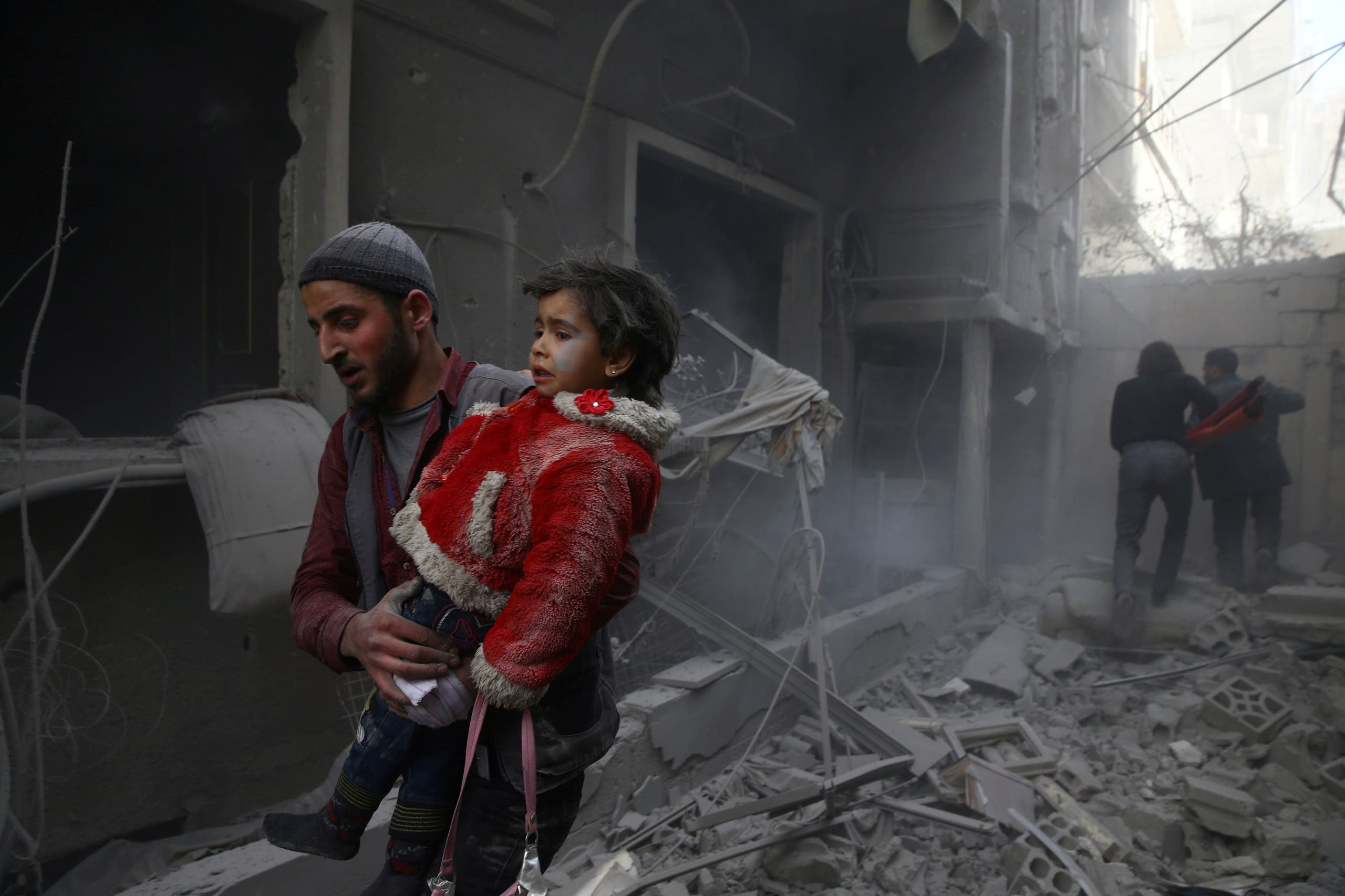 A man holds a child after an airstrike in the besieged town of Douma on February 7, 2018. (Reuters)