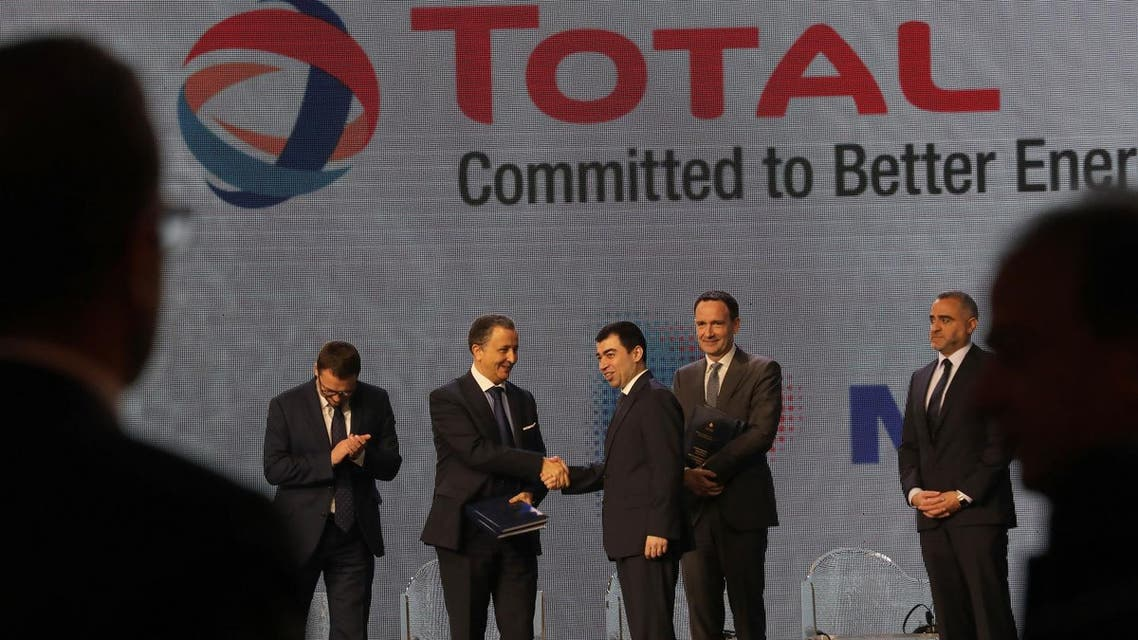 Lebanon's Energy Minister Cesar Abi Khalil (center) is handed a document by Fouad al-Kreikshi Vice Chairman for Middle East during Lebanon's first offshore oil and gas contract ceremony in Beirut on February 9, 2018. (AFP)