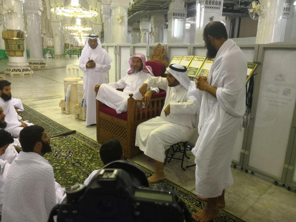 A religious scholar answers questions from people with hearing disabilities. (Saudi Gazette)