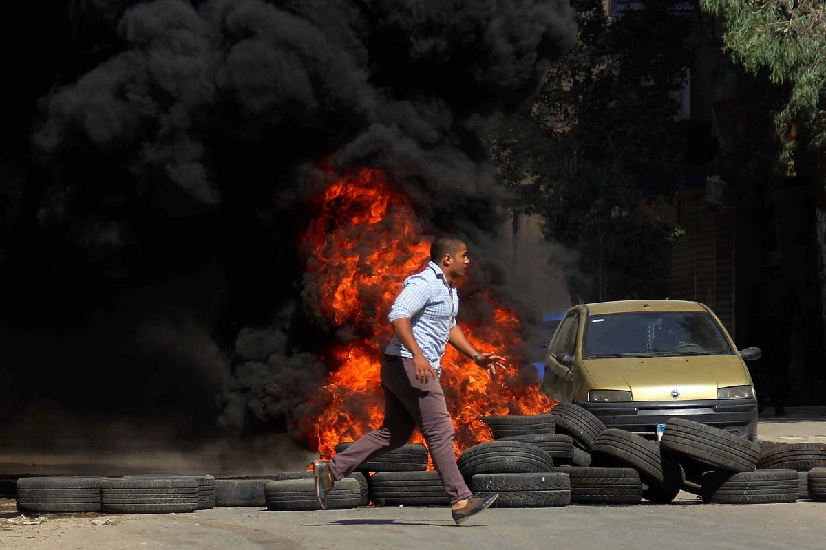 A man runs past burning tires set on fire during clashes between the security forces and supporters of the Muslim Brotherhood outside Al-Azhar University in Cairo, Egypt, Friday, May 23, 2014. (AP)