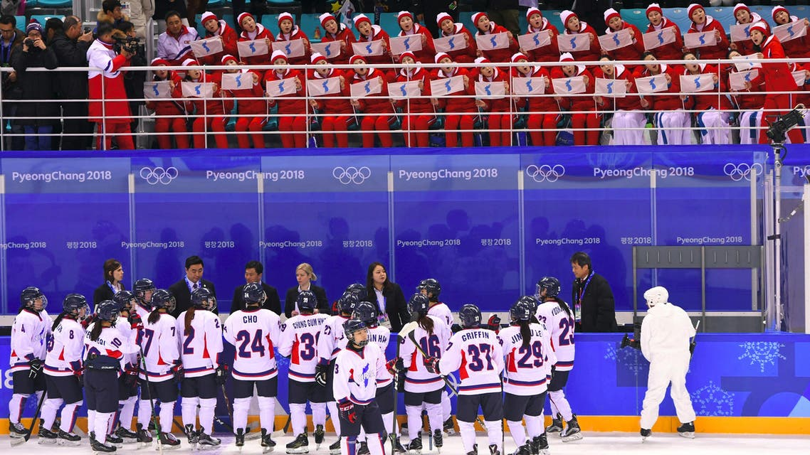 Unified Korea's team gather under the tribunes where North Korea's cheeleaders are seated during the women's preliminary round ice hockey match between Switzerland and the Unified Korean team during the Pyeongchang 2018 Winter Olympic Games at the Kwandong Hockey Centre in Gangneung on February 10, 2018.  Brendan Smialowski / AFP