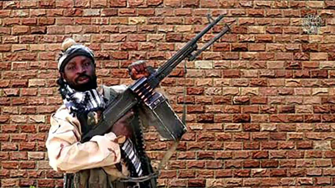 In this video grab made on January 15, 2018 from a video released the same day by Islamist militants group Boko Haram shows Boko Haram factional leader Abubakar Shekau holding a heavy machine gun. The new video shows at least 14 of the schoolgirls abducted from the northeast Nigerian town of Chibok in April 2014. The jihadists seized 276 students from the Government Girls Secondary School in the mostly Christian town in Borno state on April 14, 2014, triggering global condemnation. Handout / BOKO HARAM / AFP