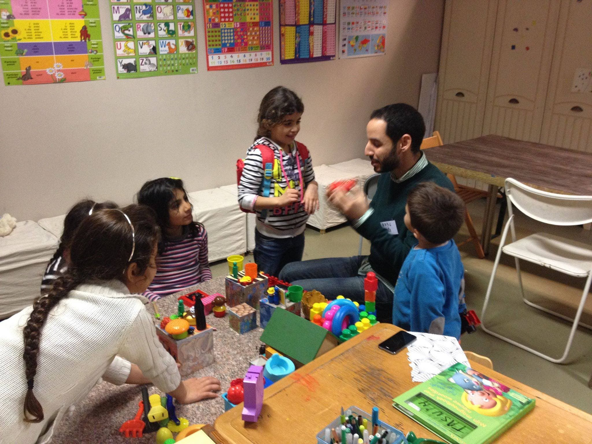 Nabil playing and teaching French to young Syrian children in Brussels. (Ghassen Fridhi/Al Arabiya)