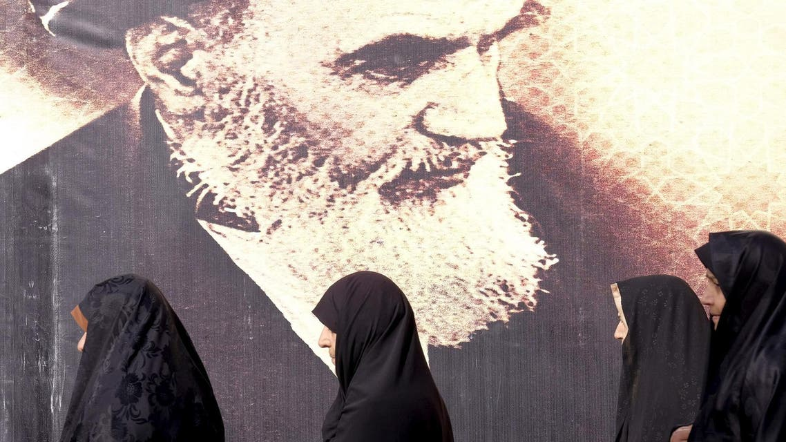Iranian women walk past a poster of Iran's late leader Ayatollah Ruhollah Khomeini during the anniversary ceremony of Iran's Islamic Revolution in Behesht Zahra cemetery, south of Tehran, February 1, 2016. (Reuters)