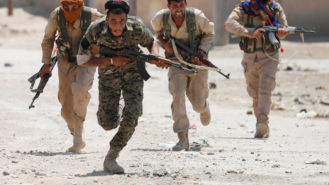 Kurdish fighters from the People's Protection Units (YPG) run across a street in Raqqa, Syria, July 3, 2017. (Reuters)