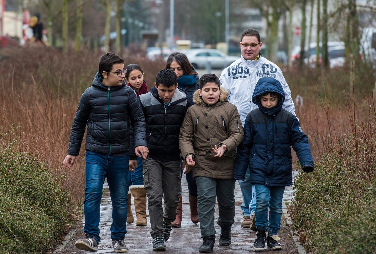 Primary school teacher Stefan Gesk (Back R) and Syrian teaching assistant Hend Al Khabbaz (Back C) take young Syrian refugee pupils (all except child on L) on an outdoor project near the Sigmund-Jaehn-Grundschule (primary school) in Fuerstenwalde, eastern Germany. (AFP)