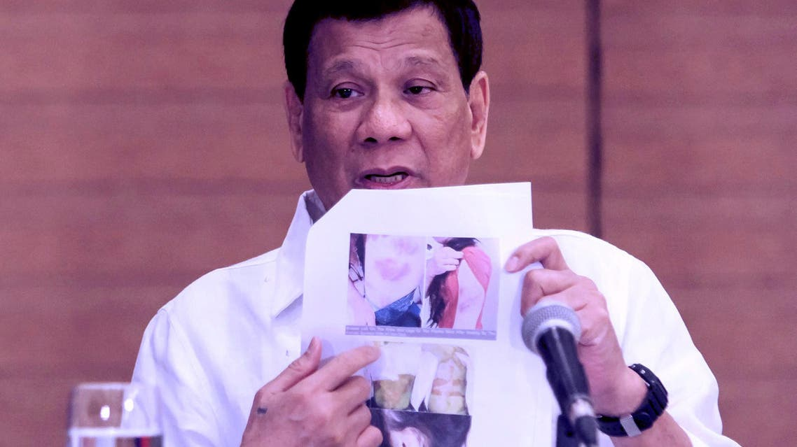 "Philippine President Rodrigo Duterte shows a photo of a Filipina worker in Kuwait, of whom he said she had been ""roasted like a pig"". (AFP)"
