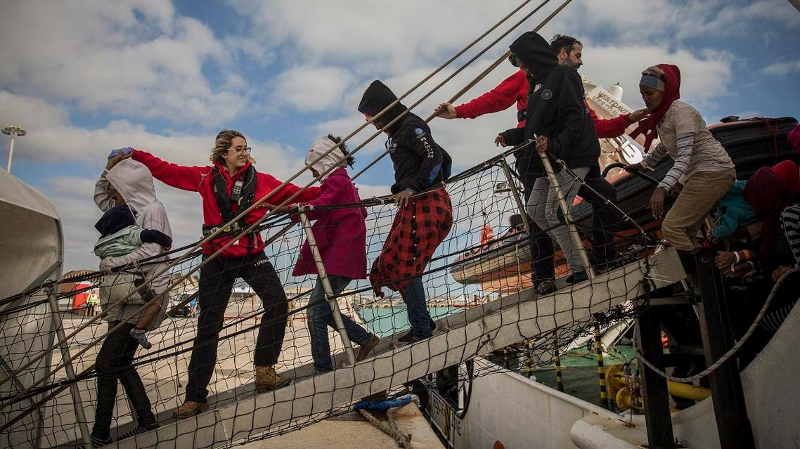 aid workers from the Spanish NGO Proactiva Open Arms help refugees and migrants to disembark from the rescue vessel, at the port of Pozzallo, in Sicily, Italy. (AP)