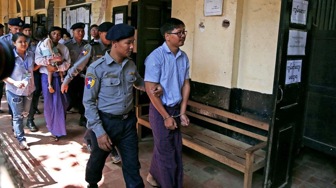 Detained Reuters journalist Wa Lone and Kyaw Soe Oo are escorted by police while arriving for a court hearing after lunch break in Yangon. (Reuters)