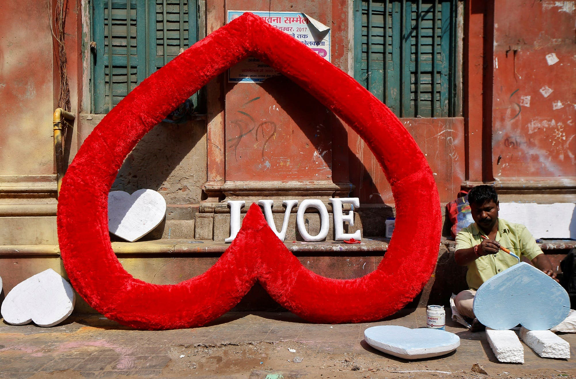 An artisan paints hearts made of polystyrene at a road side workshop ahead of Valentine's Day, in Kolkata on February 8, 2018. (Reuters)