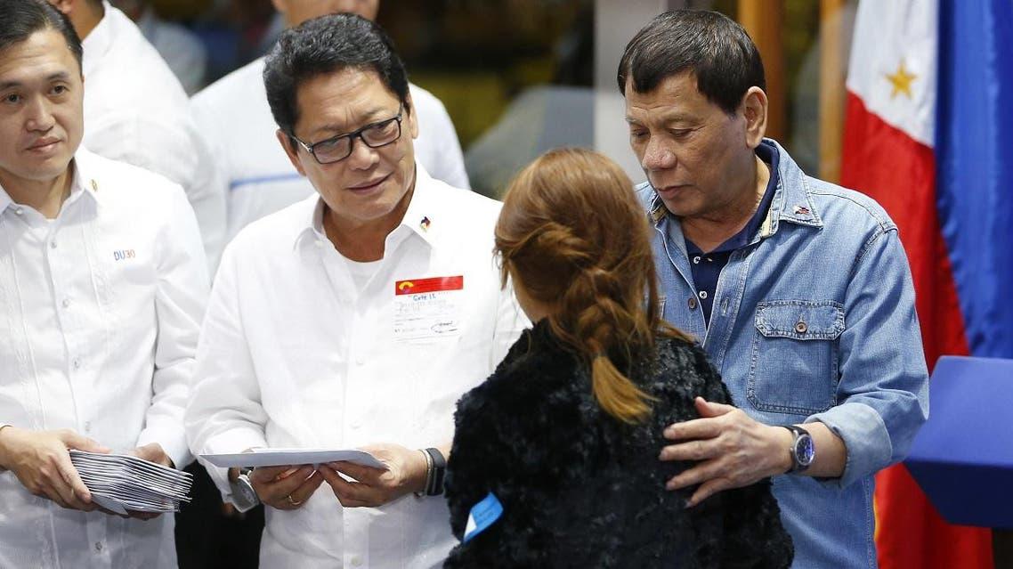 Philippine President Rodrigo Duterte hands cash gifts to Filipino Overseas Workers who were repatriated from Kuwait. (AP)