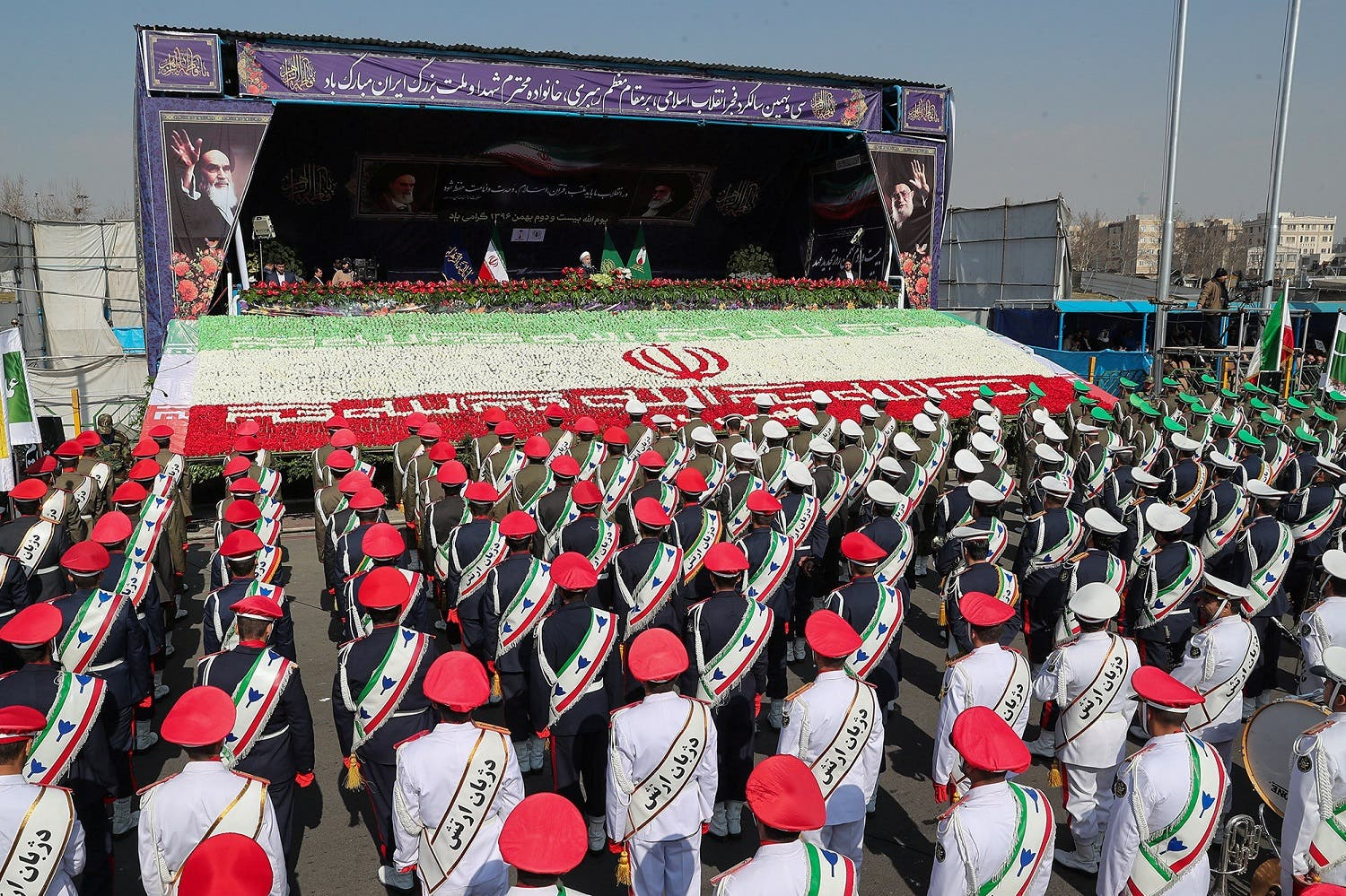 Iranian President Hassan Rouhani gestures as members of Iranian armed forces take part in a rally in Tehran, on February 11, 2018. (Reuters)