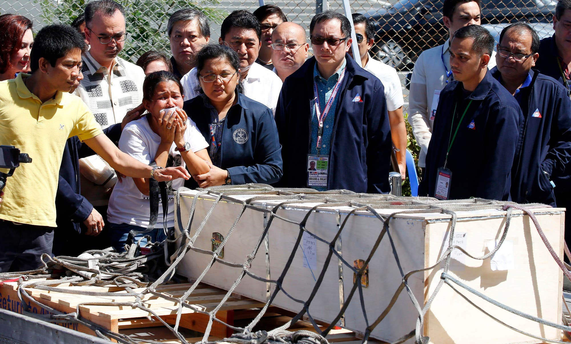 Jessica Demafelis, the sister of Joanna Demafelis who was found dead in a freezer in Kuwait, cries as the wooden casket of her remains arrives at the Ninoy Aquino International Airport Friday, Feb. 16, 2018